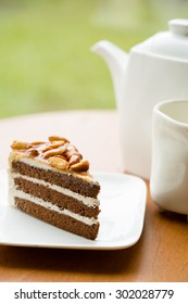 A Slice of Coffee Almond Cake on white plate with tea set, blurry background