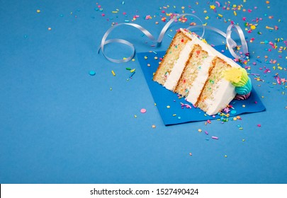 Slice of confetti Birthday cake   with buttercream icing and Sprinkles over a blue background.
