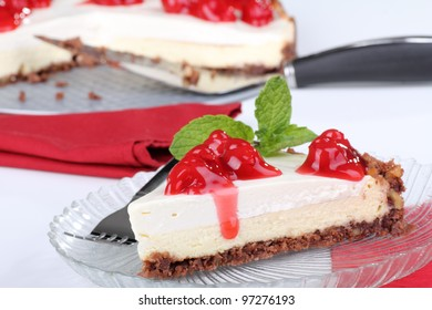 Slice of cream cheese cake with cherries and a mint leaf on top on a glass plate