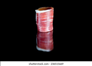 Slice of cured iberico ham isolated over black background with reflections