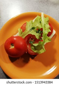 A slice of dark bread with butter, cheese lettuce, tomato and some thyme on an orange plate on a grey table. Half of ripened tomato has the stem up. A water drop and some crumbs on the dish