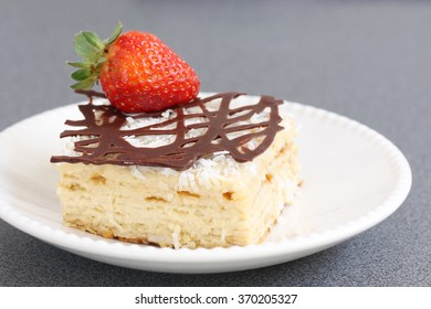 slice of decorated with chocolate and strawberry napoleon cake, served on white plate