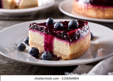 A slice of delicious blueberry cheesecake with fresh blueberries on a rustic wood table top.