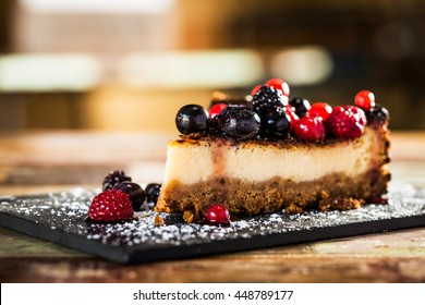Slice of delicious cheesecake with berry fruit on a wooden table.