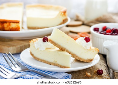 Slice of delicious cheesecake with whipped cream and berry on a wooden table