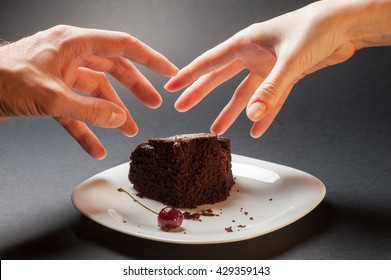 Slice of delicious chocolate cake with cherry on a white plate on a dark background. Male and female hand trying to grab a piece of cake. Greed for sweets concept with hand and chocolate cake.