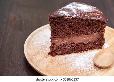 Slice of delicious chocolate cake in dish on wooden table.