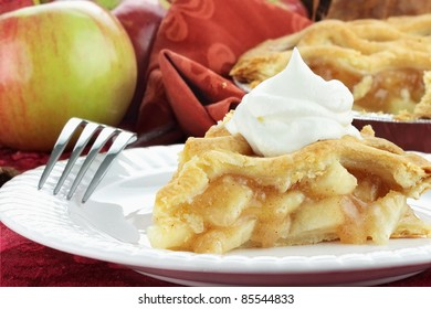 Slice of delicious fresh baked apple pie with whipped cream. Selective focus on slice of apple pie with soft blurred background.