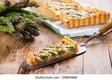 Slice of delicious home made asparagus quiche with pecorino and bacon on rustic wooden background. Selective focus.