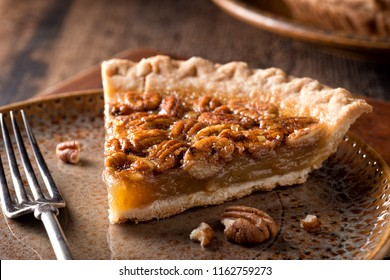 A slice of delicious home made pecan pie on a rustic table top.