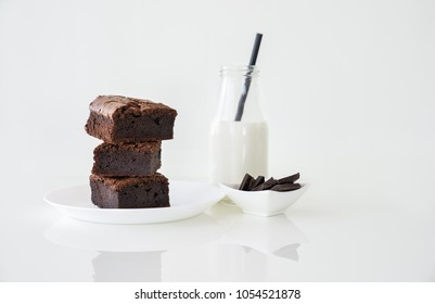 Slice of delicious homemade chocolate brownie served on white plate. Served with glass of milk with green white stripe straw. Taken on a white background.