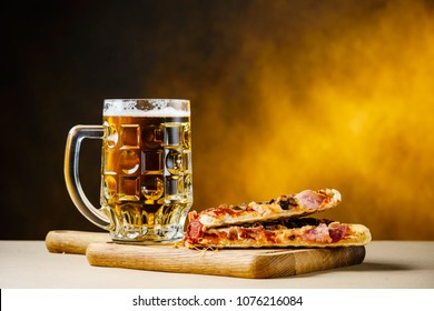 Slice of delicious homemade pizza served with light cold beer on the wooden board on yellow brown background. Pizza time