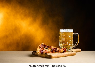 Slice of delicious homemade pizza served with light cold beer on the wooden board on yellow brown background with copyspace