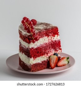 Slice of delicious homemade red velvet cake with cream , strawberries and red currants on a plate on white background. Copy space for text.