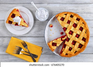 slice of delicious homemade sour cherry pie on plate. Bowl with whipped cream, dessert forks and whole tart on wooden table, classic recipe, view from above