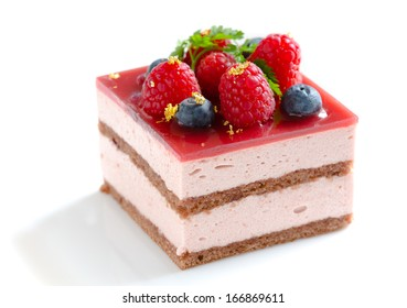 Slice of delicious layered and glazed raspberry mousse cake decorated with fresh blueberries, raspberries, sprig of chervil, and pieces of edible gold leaf