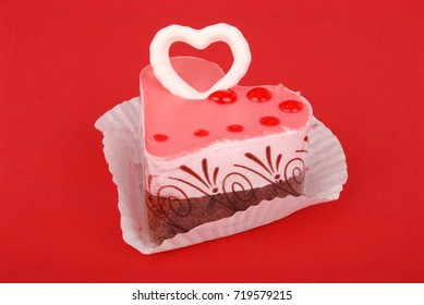 Slice of delicious layered and glazed raspberry and cherry mousse cake isolated on red background