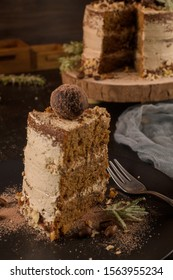 Slice of delicious naked coffee and hazelnuts cake on table rustic wood kitchen countertop.