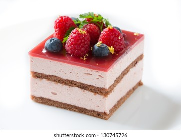 Slice of delicious raspberry mousse cake made from layers of chocolate genoise, glazed with raspberry jelly, and decorated with blueberries, raspberries, sprig of chervil, and pieces of gold leaf