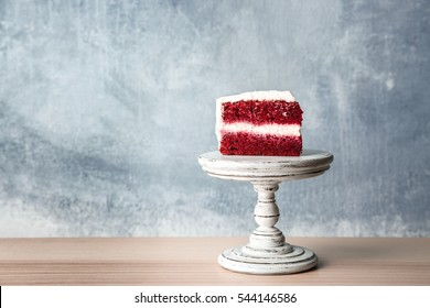 Slice of delicious red velvet cake on wooden stand