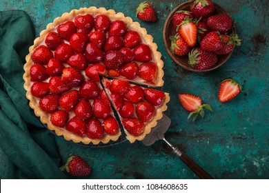 slice of delicious strawberry tart on green background, top view
