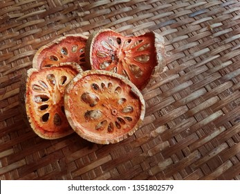 Slice dried bael is an ingredient of bael juice, being red brown golden color. Tropical Thai  Asian  herbal drinks and beverage. The bael shows in the basket background in local wooden texture in Thai