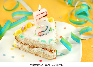 slice of fifth birthday cake with lit candle, confetti, and ribbon