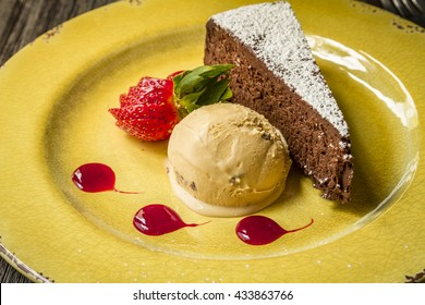 Slice of flourless chocolate cake dessert with salted caramel ice cream siiting on yellow plate with strawberry slices and sauce