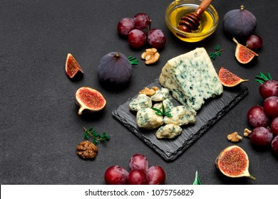 Slice of French Roquefort cheese and fruits on stone board