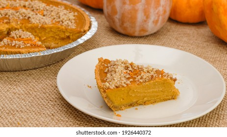 Slice of fresh baked homemade pumpkin pie decorated with crushed nuts and orange zest close up on a plate  on rustic background