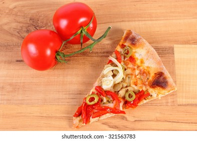 Slice of fresh baked vegetarian pizza and tomatoes on wooden table, italian cuisine, concept of fast food