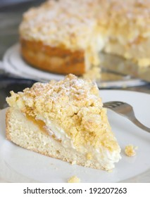 Slice of fresh home made apricot cake or tart with cheese and yeast dough, covered with crumble