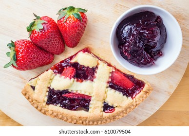 slice of fresh homemade cherries tart and  strawberry on wooden table.closeup