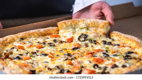 A slice of fresh hot vegetarian pizza with a stretch of mozzarella cheese in the cook's hand.