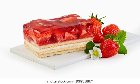 Slice of fresh strawberry tart with layered pastry and cream topped with berries and ripe fruit on a white board and background for advertising or a menu