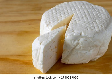 slice of fresh white mine cheese on the wooden board.