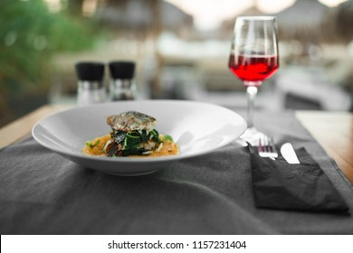 slice of fried fish with yellow mashed potatoes and mint on a white plate next to appliances with a red wine glass