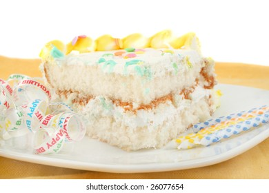 slice of frosted festive birthday cake with candles and ribbon