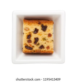 Slice of fruit cake in a square bowl isolated on white background