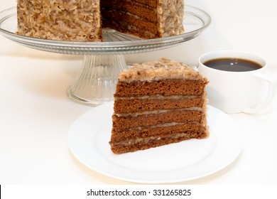 Slice of german chocolate cake removed from whole cake which is in background along with cup of coffee.  Isolated on white background.