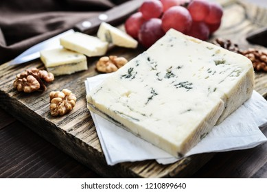 Slice of Gorgonzola cheese on cutting board served with grape and nuts closeup