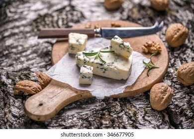 Slice of gorgonzola cheese with rosemary and nut
