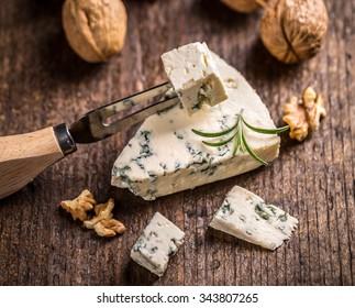 Slice of gorgonzola cheese with rosemary and walnut