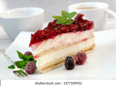 Slice of gourmet fresh raspberry cake on a plate with fresh summer raspberries, ginger mint in and a white flower.