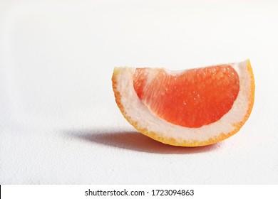 Slice of grapefruit on a white background.
