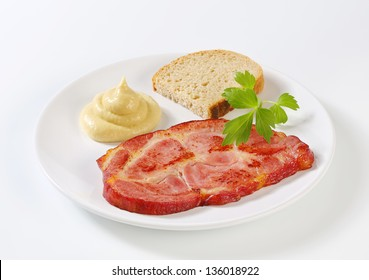 Slice of grilled pork neck with bread and mustard on a plate