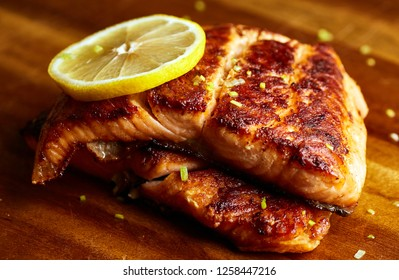 Slice of grilled salmon steak with lemon and leek on a wooden board