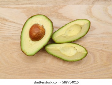 Slice and half avocado isolated on wooden board