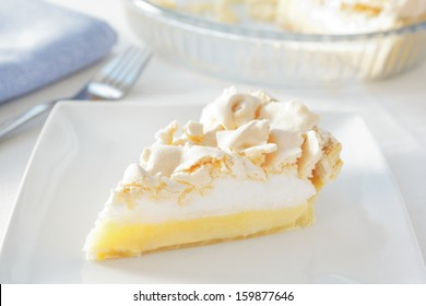 a slice of home made lemon meringue pie on a plate, with the pie dish and a fork and napkin in the background