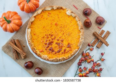 slice of home made pumpkin pie on plate with pumpkins